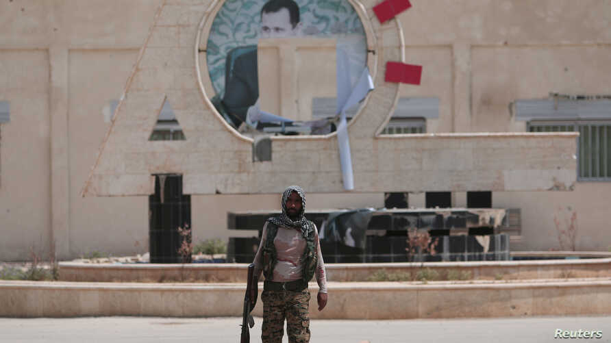 A Kurdish fighter from the People's Protection Units (YPG) carries his weapon as he walks at the faculty of economics where a defaced picture of Syrian President Bashar al-Assad is seen in the background, in the Ghwairan neighborhood of Hasaka, Syria
