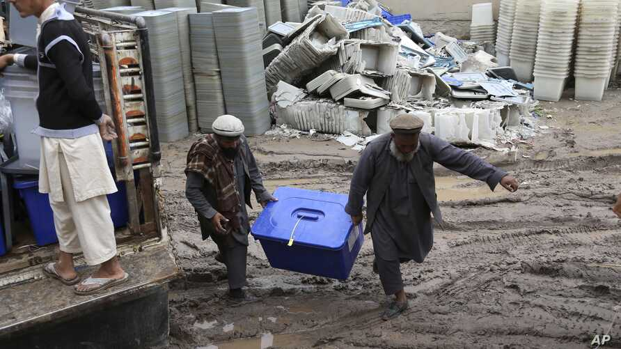 Afghan workers of the election commission office unload a ballot box from a truck after votes in Jalalabad, east of Kabul, Afghanistan, Sunday, April 6, 2014.