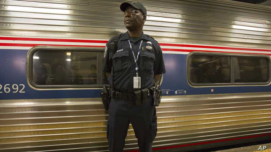 An Amtrak police officer stands guard outside Train 110, May 18, 2015, at Philadelphia's 30th Street Station. The train bound for New York was the first northbound train from the city since a May 12 derailment killed 8 people and injured dozens.