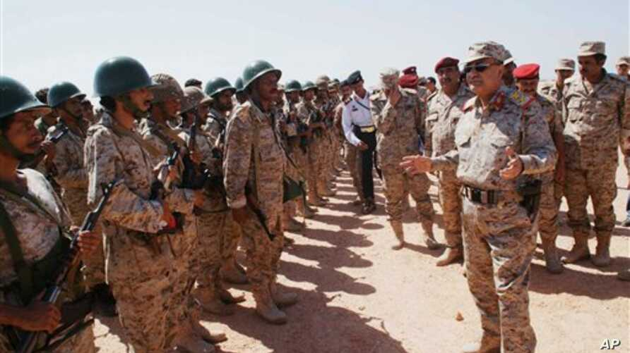 Yemeni Defense Minister Mohammad Nasser Ahmad, right, inspects troops at a military site in the southern province of Shabwa, April 28, 2014.