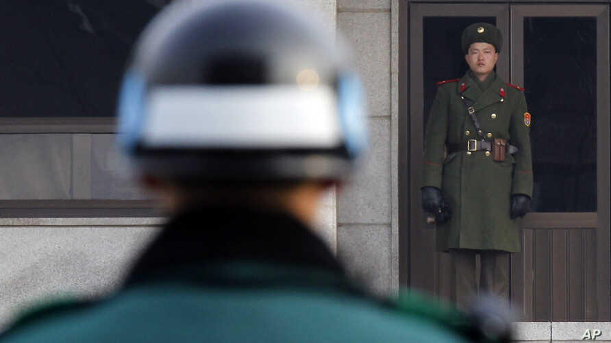A North, right, and a South Korean soldier look at each other's sides at the Panmunjom (DMZ) that separates the two Koreas since the Korean War, in Paju, South Korea, December 28, 2011.