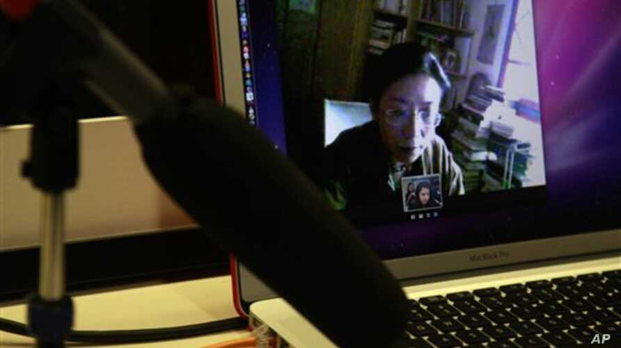 FILE - Tibetan and activist Poet Tsering Woeser appears on computer screen, top, during online video chat with The Associated Press, Beijing, March 1, 2012.