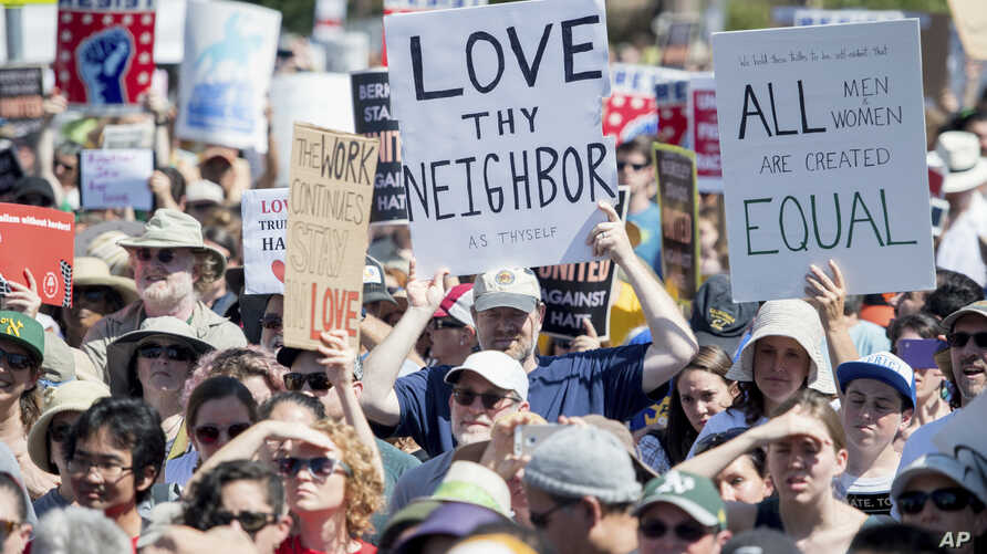 People hold up signs and shout while listening to speakers during a rally against hate in Berkeley, California, Sunday, Aug. 27, 2017.
