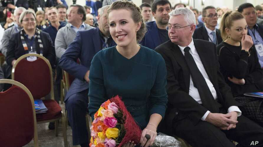 Russian celebrity TV host Ksenia Sobchak, who wants to challenge Russian President Vladimir Putin in the March 18 presidential election, smiles after receiving a bouquet of flowers at the meeting of her supporters in Moscow, Russia, Dec. 23, 2017.