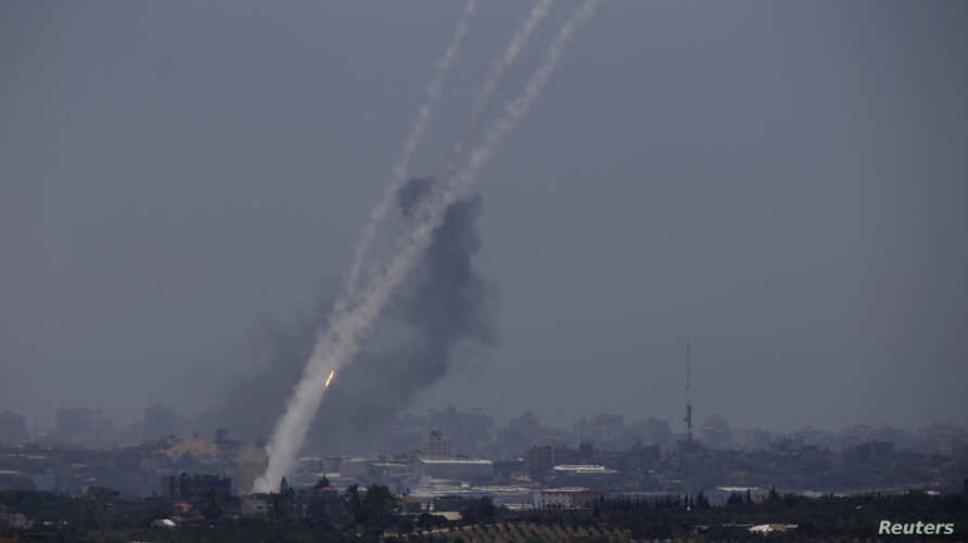 Smoke trails are seen as rockets are launched towards Israel from the northern Gaza Strip, July 10, 2014.