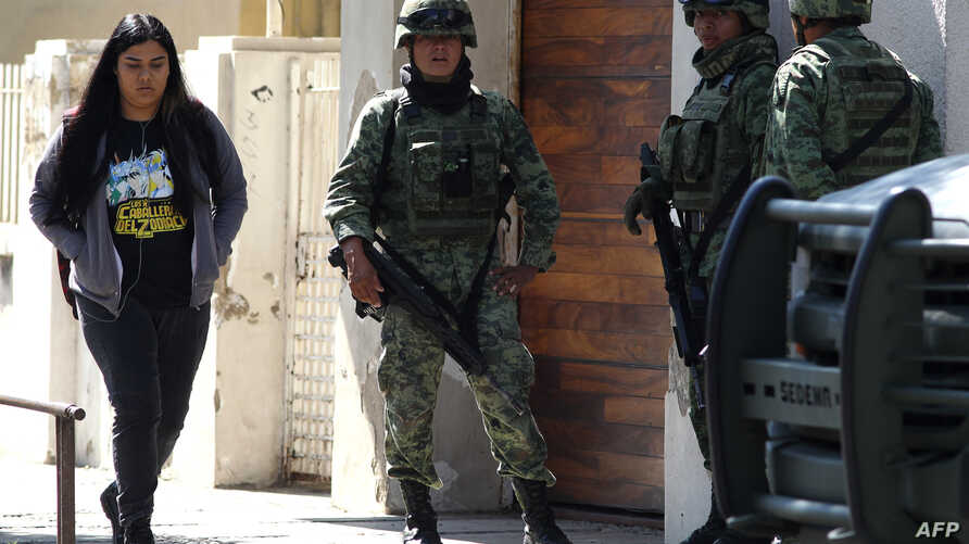 Members of the Mexican Army stand guard outside the U.S. Consulate in Guadalajara, Mexico, Dec. 1, 2018, after an attack with an explosive device damaged a wall but injured no one.