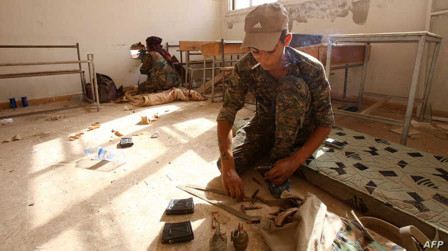 Members of the Kurdish People's Protection Units (YPG) take position in a classroom in the village of Maarouf in the northeastern Syrian province of Hasakeh as they battle Islamic State group jihadists, July 16, 2015.