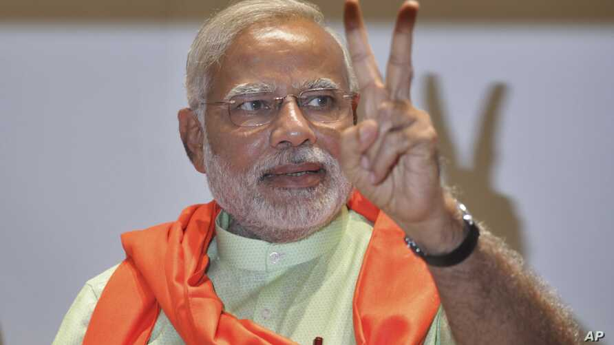Gujarat state chief minister and the prime ministerial candidate of India's main opposition Bharatiya Janata Party (BJP), Narendra Modi, flashes victory sign to the media during a meeting of the BJP members of Gujarat's state legislature in Gandhinag
