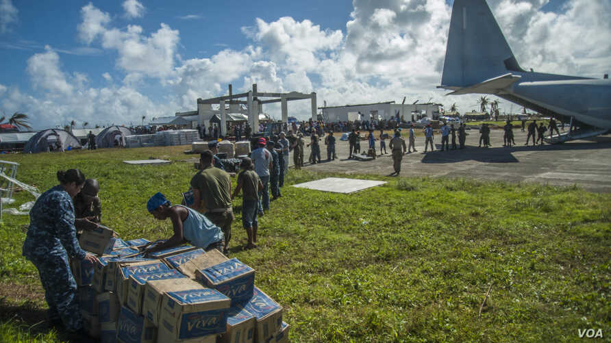 Sailors assigned to the U.S. Navy's forward-deployed aircraft carrier USS George Washington (CVN 73), Marines assigned to the 3 Marine Expeditionary Brigade (3 MEB), and Philippine civilians unload relief supplies in support of Operation Damayan. (US