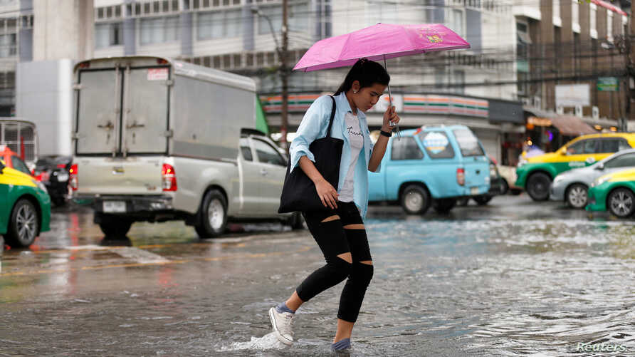 A woman walks on a flooded street in Bangkok, Thailand,  Sept. 24, 2018.