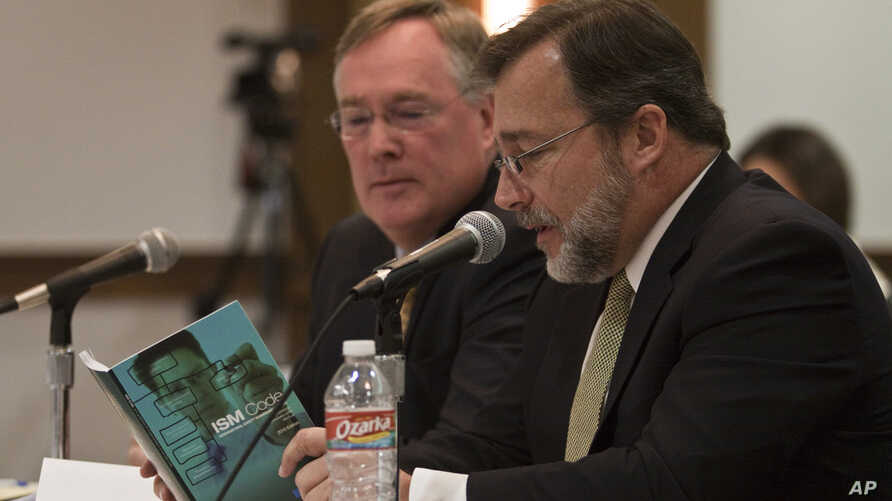Attorney Tim Johnson, left, and Jerry Canducci, right, Transocean ISM manager, read a ISM Code booklet at the request of the hearing panel at the sixth session of BP oil spill hearings in Houston, December 9, 2010.