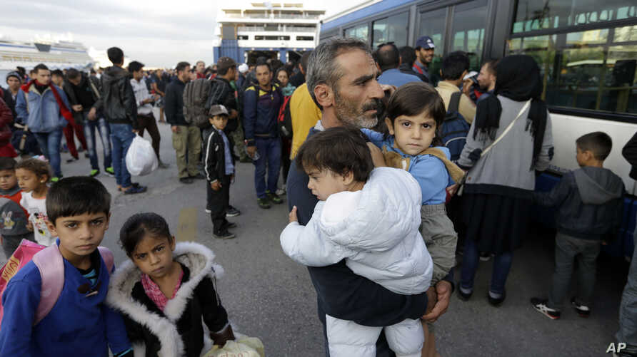 A Syrian man holds his two children as the other two family members follow him after their arrival from the Greek island of Lesbos at the Athens' port of Piraeus, Wednesday, Sept. 30, 2015.