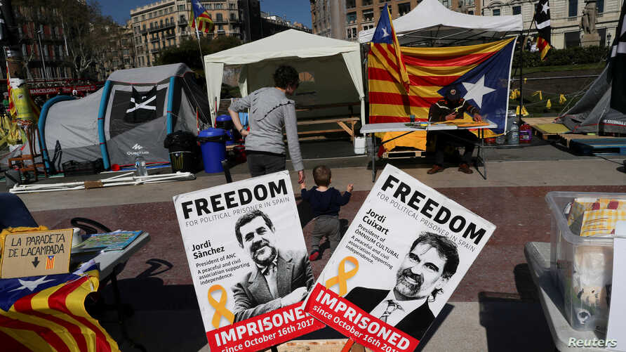 FILE - Banners with the photos of jailed Catalan pro-independence leaders Jordi Sanchez and Jordi Cuixart are displayed at a protest rally in Barcelona, Spain, March 28, 2018.