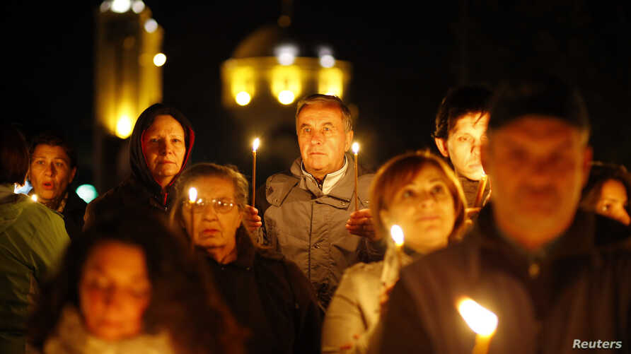 FILE - Believers light candles to mark 1,700 years since the Edict of Milan, when Roman emperor Constantine issued instructions to end the persecution of Christians, in the southern Serbian city of Nis, Oct. 5, 2013.