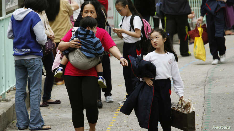 A foreign domestic helper carrying a child walks with another child outside a school in Hong Kong, Feb. 26, 2013.