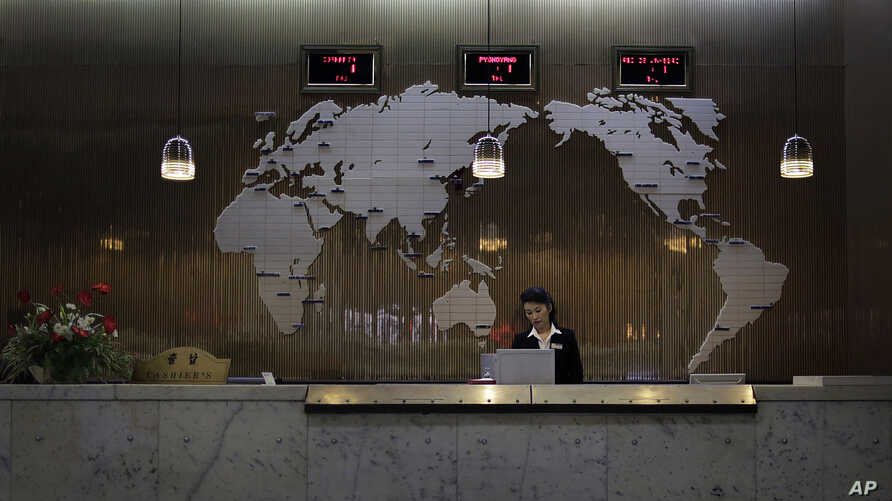 FILE - A staff member stands at the reception desk of a hotel, backdropped by a world map, in Pyongyang, North Korea, Oct. 23, 2014.