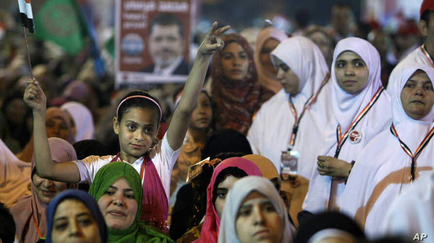 A young girl flies an Egyptian national flag as she listens to Mohammed Mursi, the Muslim Brotherhood's presidential candidate, at a rally in Cairo, May 20, 2012.