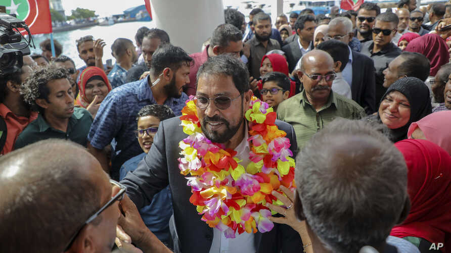 FILE - Maldives opposition leader Qasim Ibrahim, center, is welcomed at the airport as he returned home from exile in Male, Maldives, Thursday, Oct. 4, 2018.