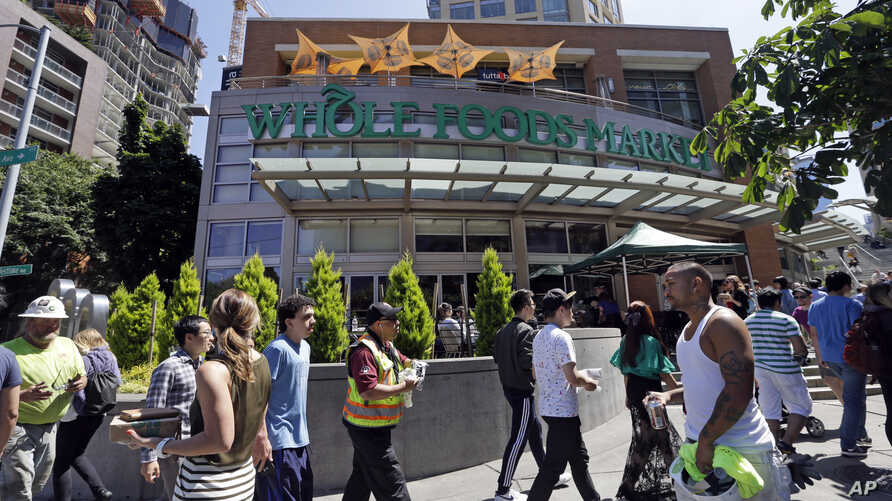 FILE - Pedestrians walk past a Whole Foods Market, just down the street from the headquarters of Amazon, in Seattle, Washington, July 11, 2017.