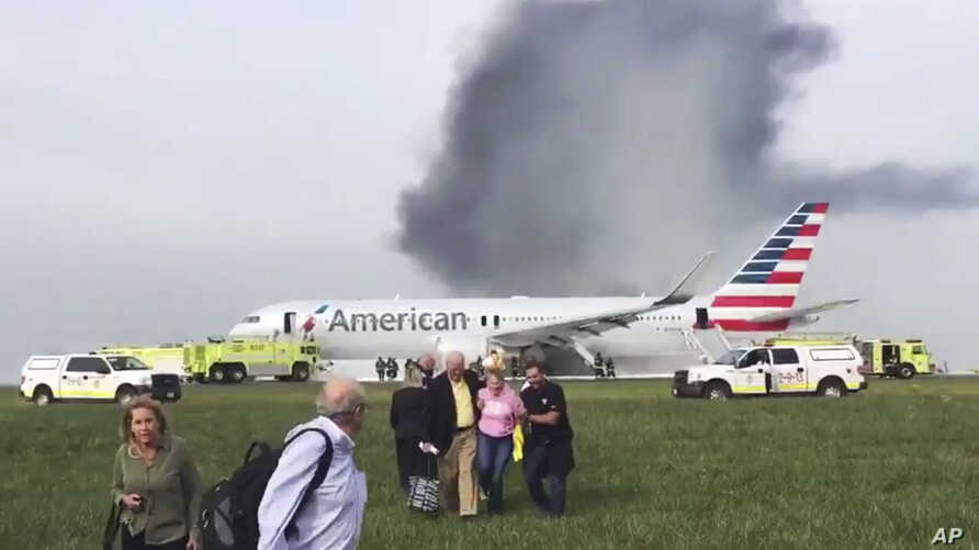 In this photo provided by passenger Jose Castillo, fellow passengers walk away from a burning American Airlines jet that aborted its takeoff and caught fire on the runway at Chicago's O'Hare International Airport, Oct. 28, 2016. Pilots on Flight 383