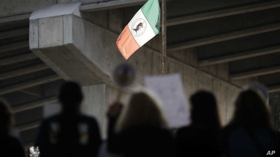People attend a rally against a scheduled upcoming visit to the area by President Donald Trump as a flag fashioned after the flag of Mexico flies over Chicano Park, March 12, 2018, in San Diego.