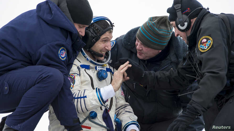 Astronaut Michael Hopkins from NASA reacts as he is helped out of the Soyuz TMA-10M capsule shortly after the landing in a remote area southeast of the town of Zhezkazgan in central Kazakhstan, March 11, 2014.