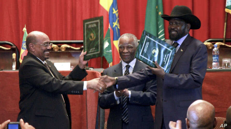 Sudan's President Omar al-Bashir, left, and South Sudan President Salva Kiir, right, shake hands on the completion of a signing ceremony after the two countries reached a deal on economic and security agreements in Addis Ababa, Ethiopia, Sept. 27, 20