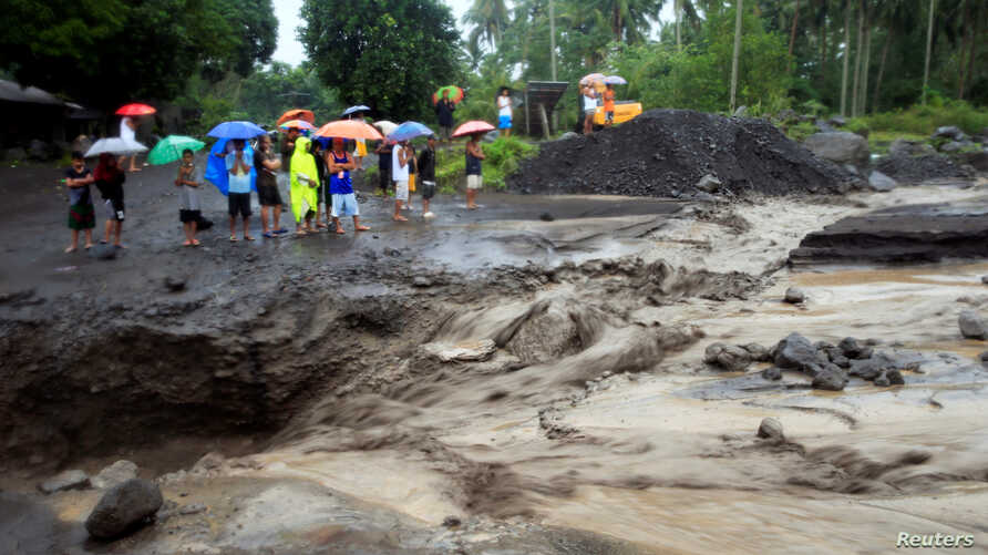 Residents watch a river of lahar flow from Mount Mayon volcano in Guinobatan, Albay province, south of Manila, Philippines, Jan. 27, 2018.