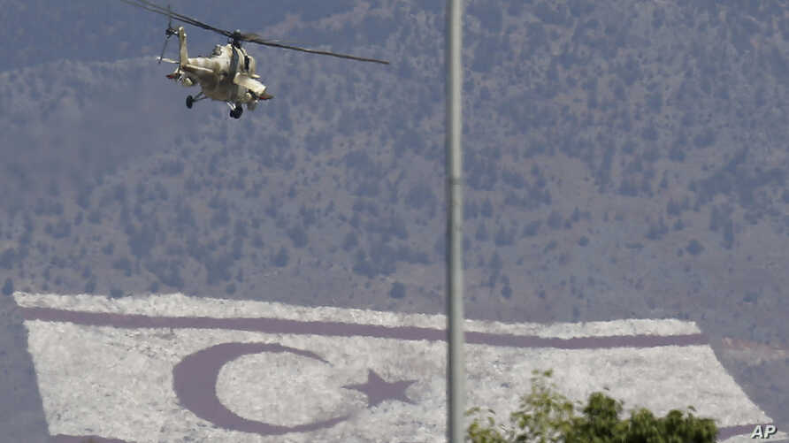 FILE - A Russian made military helicopter of Cypriot air forces flies over the military parade as a giant painting of Turkish Cypriot breakaway flag is seen on Pentadaktilos mountain at the north part in capital Nicosia in the divided island of Cypru