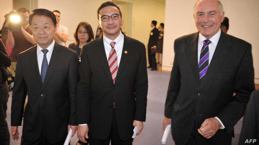 Chinese Transport Minister Yang Chuantang (L), Malaysia's Transport Minister Hishammuddin Hussein (C) and Australia's Transport Minister Warren Truss (R) leave a press conference about missing Malaysia Airlines flight MH370, at Parliament House in Ca