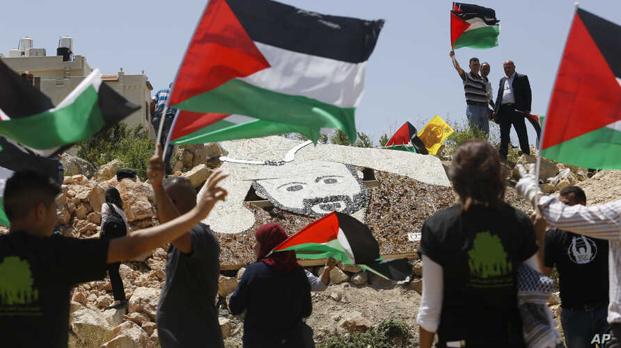 Palestinian activists stand around a 5x4 meter (16.5x13 feet) mosaic portrait of Marwan Barghouti near an Israeli military installation in the West Bank city of Ramallah, May 9, 2017.