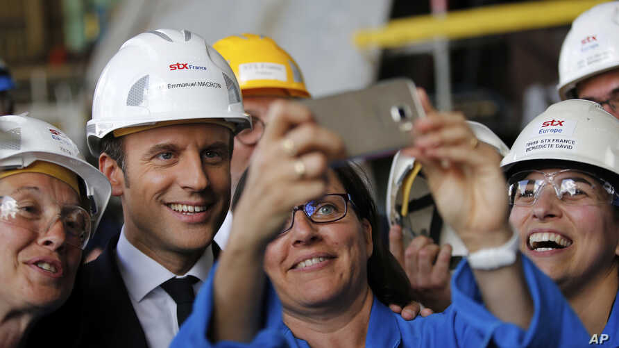 French President Emmanuel Macron poses for selfies as he visits the MSC Meraviglia cruise ship at the STX shipyard site in Saint-Nazaire, western France, May 31, 2017.