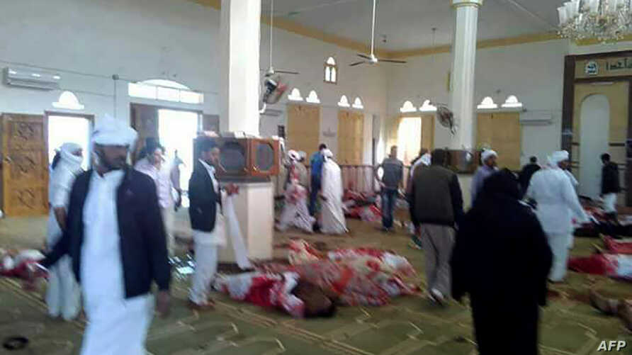WARNING: Graphic content - Egyptians walk past bodies following a gun and bombing attack at the Rawda mosque, roughly 40 km west of North Sinai capital of El-Arish, on Nov. 24, 2017.