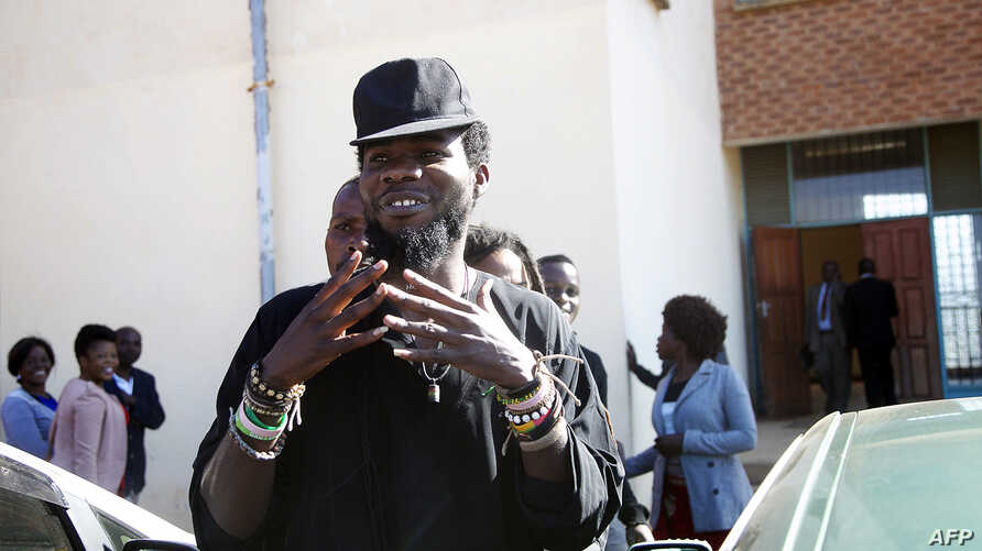 """Zambian Musician Chama Fumbe, popularly known as Pilato, gestures as he leaves the Magistrates Court in Lusaka, June 24, 2015, after a hearing in his trial on charges of  """"conduct likely to breach the peace""""."""