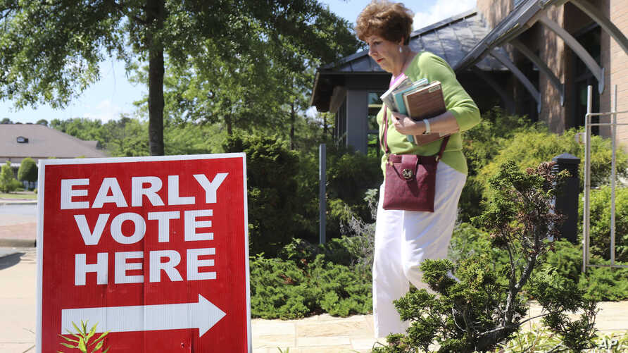 A library patron passes by a precinct sign outside the Roosevelt Thompson Library, May 7, 2018, as early voting opened in Little Rock, Arkansas.