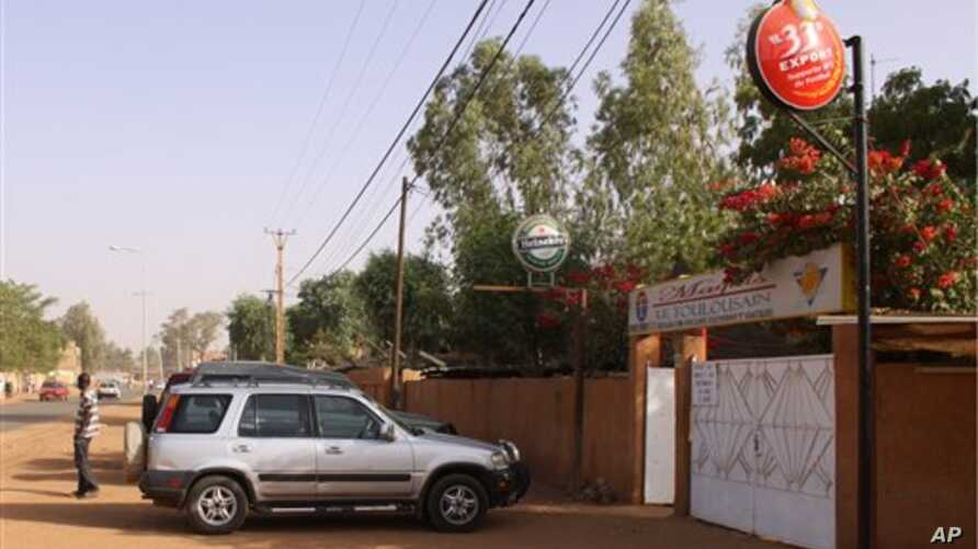 A man stands outside the front gate to the Toulousain restaurant, from inside which witnesses say two French nationals were kidnapped at gunpoint late Friday by turbaned men, in Niamey, Niger, 08 Jan 2011