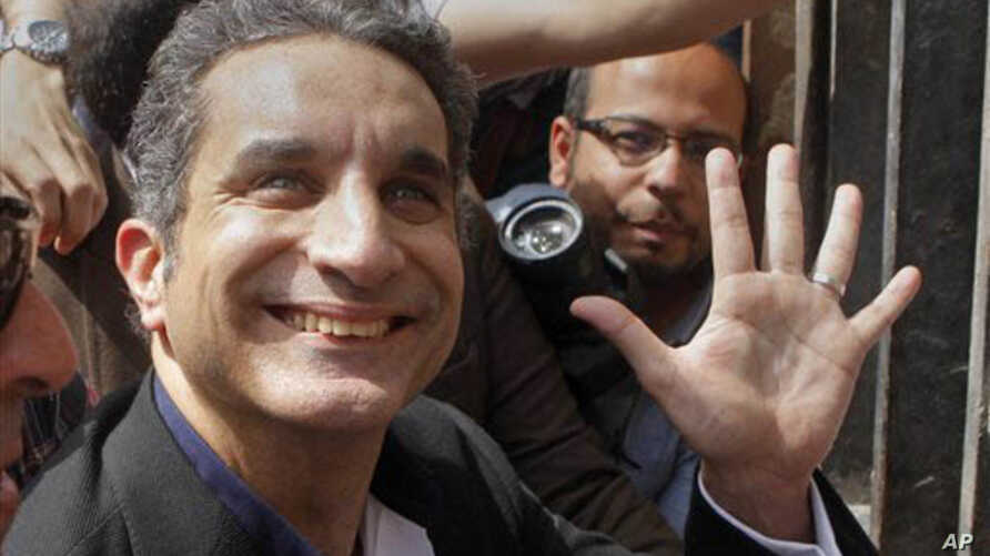 Bassem Youssef, Egyptian TV satirist, waves to supporters as before talks with authorities about charges he insulted Islam and the nation's president.