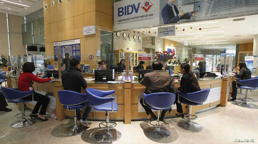 FILE - Clients sit in a branch of the Bank for Investment and Development of Vietnam (BIDV) in Hanoi.