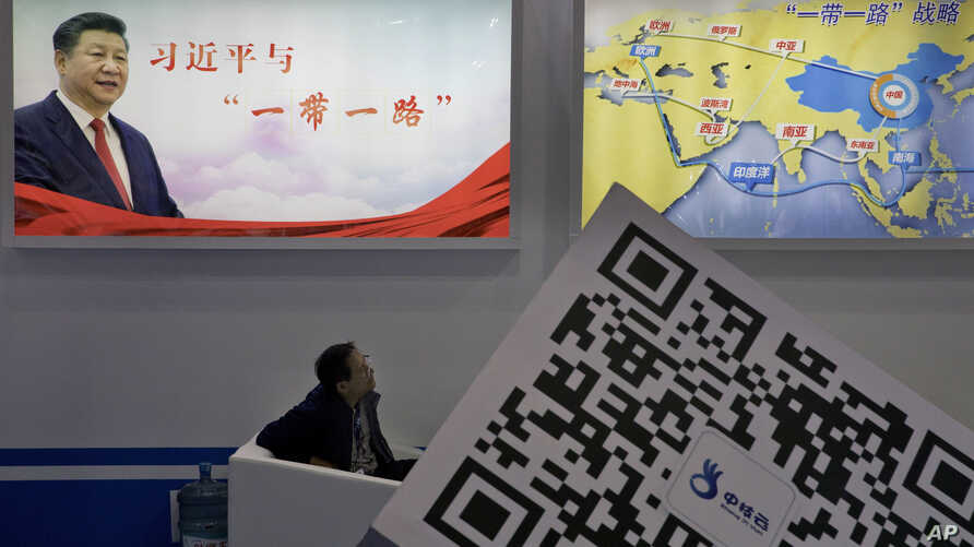 """An attendee at a conference looks up near a portrait of Chinese President Xi Jinping with the words """"Xi Jinping and One Belt One Road"""" and """"One Belt One Road strategy,"""" in Beijing, April 28, 2017. The """"Belt and Road Forum"""" opening Sunday is the l..."""