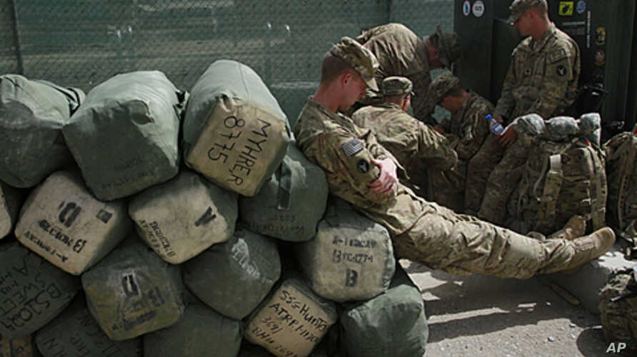 A U.S. soldier with Task Force Red Horse leans on baggage, as they wait out side of the customs office to leave Afghanistan at the U.S. base in Bagram, north of Kabul, Afghanistan,  July 14, 2011