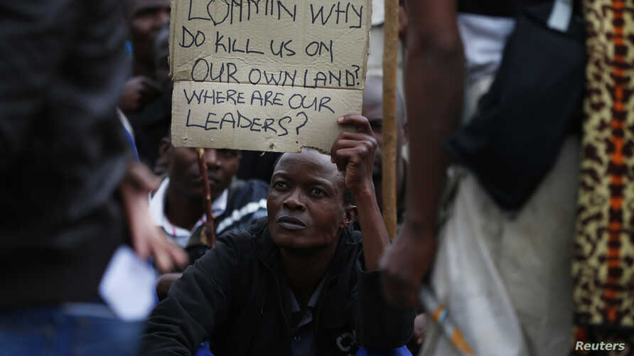 A mineworkers holds up a sign during a march at Lonmin's Marikana mine in South Africa's North West Province, September 5, 2012.