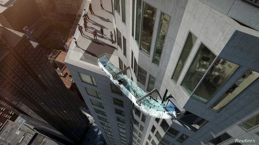 """An artist rendering of the """"Skyslide"""" attraction, an outdoor glass slide positioned close to 1,000 feet above downtown Los Angeles, California, is shown in this image released by OUE Skyspace, March 2, 2016"""