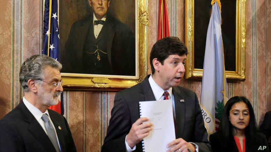 U.S. Attorney Steven Dettelbach, center,  holds up the settlement agreement with the City of Cleveland a news conference, May 26, 2015, in Cleveland.