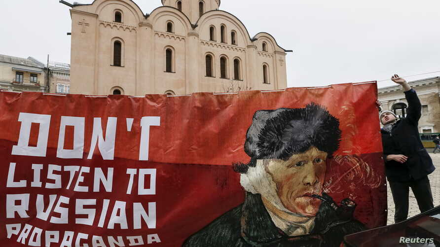 An activist holds a banner with a portrait of Dutch artist Vincent van Gogh as he demonstrates outside the Dutch embassy in Kyiv, Ukraine, Feb. 5, 2016. The activists demanded that Dutch people ignore what they say are Russian propaganda, ahead of an