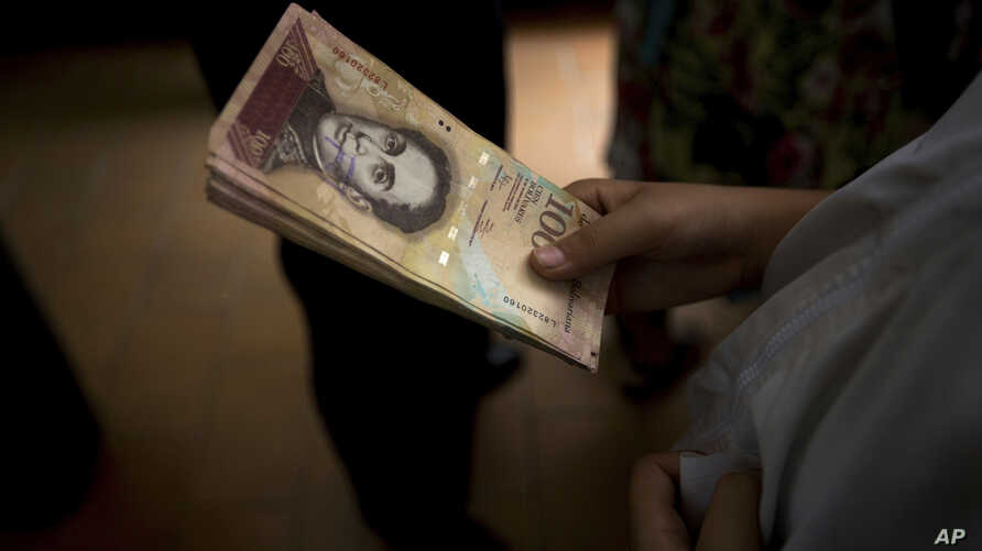 A customer holds a stack of 100-bolivar notes  at a bakery in downtown Caracas, Venezuela, Dec. 12, 2016. Venezuelans were rushing to spend their 100-bolivar notes after a surprise announcement that they will be taken out of circulation. More of the