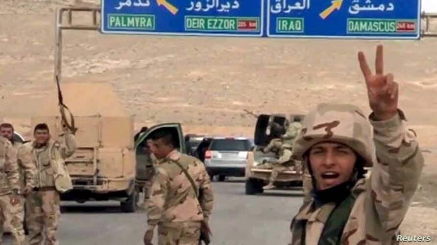 Forces loyal to Syria's President Bashar al-Assad gesture as they advance into the historic city of Palmyra in this picture provided by SANA, March 24, 2016.