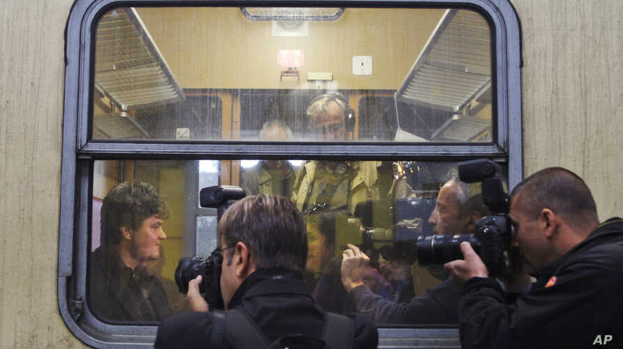 Musician Markus Rindt a 1989 German refugee is surrounded by media after boarding a train in Prague, Czech Republic, Oct. 1, 2009. A train that once carried East Germans refugees to freedom has left Prague to commemorate the 20th anniversary of the t