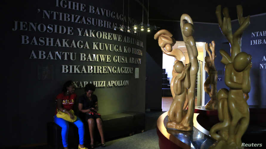 Rwandan people sit inside the Kigali Genocide Memorial Museum as the country prepares to commemorate the 20th anniversary of the 1994 genocide in the capital Kigali, April 5, 2014.