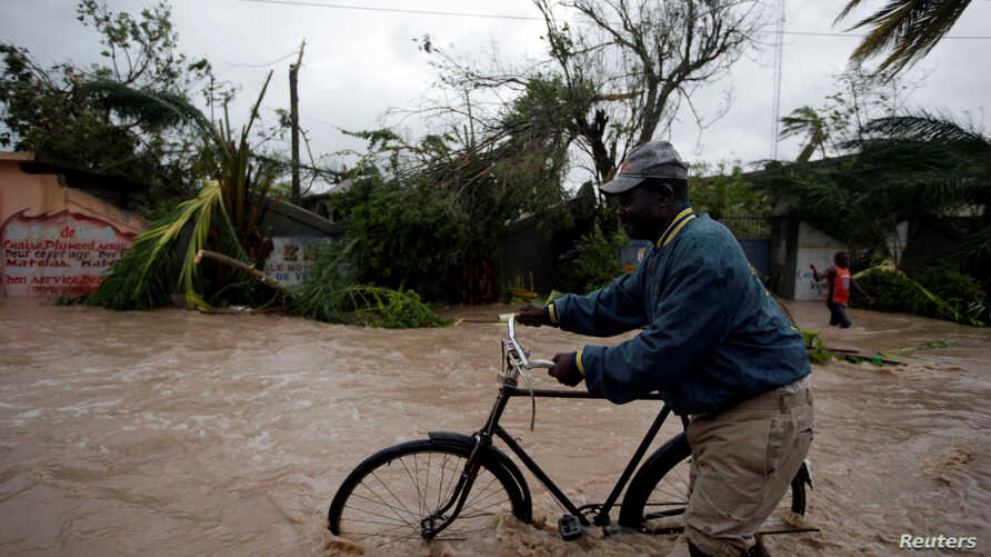 A man pushes a bicycle in a flood zone after Hurricane Matthew passed through Les Cayes, Haiti, Oct. 4, 2016.