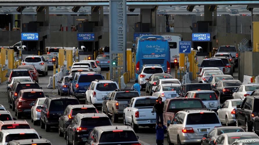FILE - Cars stand in multiple lines as they wait to be inspected by U.S. Border Patrol officers to enter from Mexico to the U.S. as the San Isidro point of entry in Tijuana, Mexico, Apr. 4, 2018.